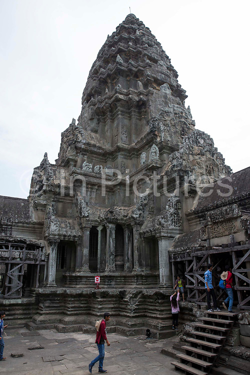 Some tourists explore around a tower of Angkor Wat in the ancient temple complex of Angkor Wat Siem Reap, Cambodia.  Angkor Wat is one of UNESCO's world heritage sites. It was built in the 12th century and is Cambodia's main tourist destination.