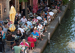 Busy outdoor summer cafes and restaurants beside canal Oudegracht in central Utrecht in the Netherlands