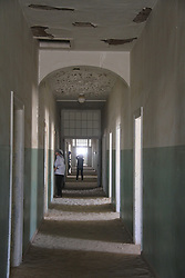 WINDHOEK, Nov. 25, 2013  Tourists walk in the corridor of the abandoned hospital in ''Ghost Town'' Kolmanskop, Namibia, Nov. 23, 2013. Kolmanskop is a ghost town in the Namib desert in southern Namibia. In 1908 a diamond was found in this area, which led to a huge and frantic diamond rush by German settlers. Driven by the enormous wealth of the first diamond miners, the residents built the village in the architectural style of a German town, with amenities and institutions including a hospital, ballroom, school, casino and even an x-ray-station. The town declined after World War I when the diamond field slowly exhausted and was ultimately abandoned in 1954. Now it is a popular tourist destination. (Xinhua/Gao Lei) (Credit Image: å© Gao Lei/Xinhua/ZUMAPRESS.com)