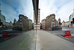 Edinburgh, Scotland, UK. 18 April 2020. Views of empty streets and members of the public outside on another Saturday during the coronavirus lockdown in Edinburgh. Leith Walk reflected in shop window shows nobody on the street. Iain Masterton/Alamy Live News