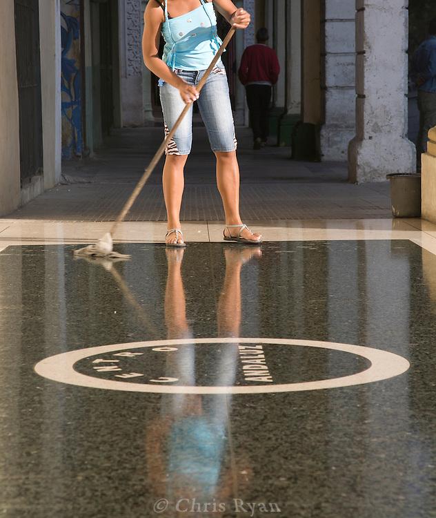 Worker mopping entry of Centro Andaluz flamenco venue, Havana, Cuba