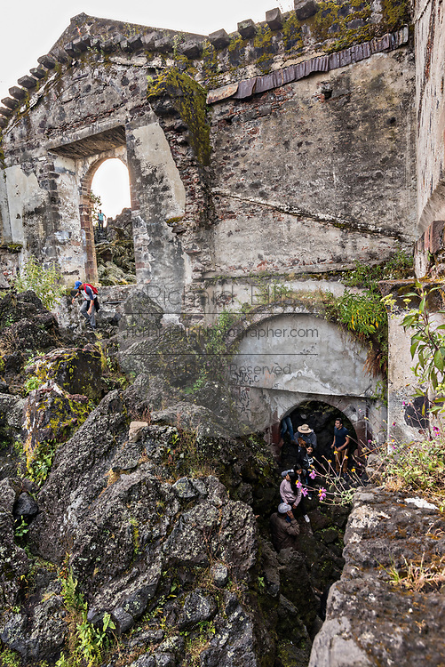 Tourists tour a room under the San Juan Parangaricutiro church poking up out of a sea of dried lava rock in the remote village of San Juan Parangaricutiro, Michoacan, Mexico. This church is the only remaining structure left buried in the eight-year eruption of the Paricutin volcano which consumed two villages in 1943 and covered the region in lava and ash.