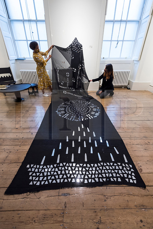 """© Licensed to London News Pictures. 08/10/2020. LONDON, UK. Staff members present """"Astral Sea III"""", 2019, by Tsedeye Makonnen.  Preview of 1-54 Contemporary African Art Fair, the leading international art fair dedicated to contemporary art from Africa and its diaspora, taking place at Somerset House.  The fair showcases the work of more than 110 emerging and established artists from Africa and is the only physical art fair taking place during Frieze Week.  Photo credit: Stephen Chung/LNP"""