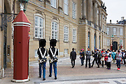 Tourists taking photograph of Royal Guard, in uniform at Royal Amalienborg Palace, Copenhagen, Denmark