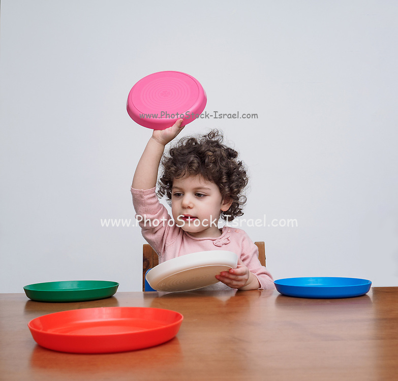A toddler plays with plastic dishes at a table