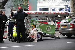 © Licensed to London News Pictures. 07/10/2019. London, UK. Extinction Rebellion protestors are cut out from a rig carrying a fake missile by police as they arrest some activists on Embankment near the Ministry of Defence in central London . Activists will converge on Westminster blockading roads in the area for at least two weeks calling on government departments to 'Tell the Truth' about what they are doing to tackle the Emergency. Photo credit: Peter Macdiarmid/LNP