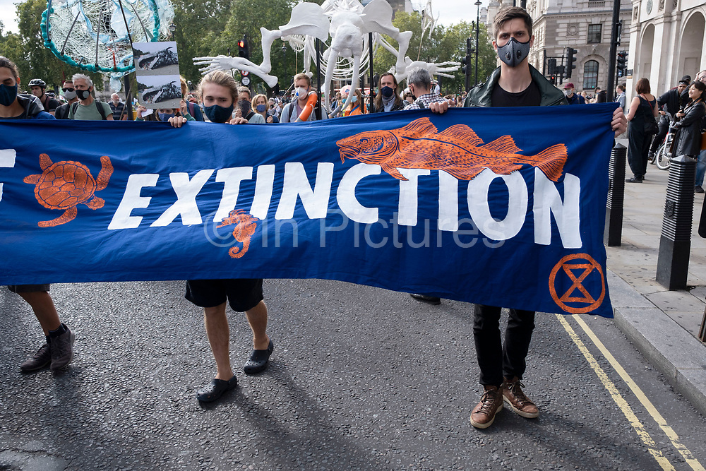 Extinction Rebellion activists with a 'Marine Extinction' banner at the Marine Rebellion march on 6th September 2020 in London, United Kingdom. Ocean Rebellion, Sea Life Extinction, Animal Rebellion and Extinction Rebellion joined together to celebrate the biodiversity found in our seas, and to grieve at the destruction of the Earth's oceans and marine life due to climate breakdown and human interference, and the loss of lives, homes and livelihoods from rising sea levels. Extinction Rebellion is a climate change group started in 2018 and has gained a huge following of people committed to peaceful protests. These protests are highlighting that the government is not doing enough to avoid catastrophic climate change and to demand the government take radical action to save the planet.