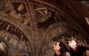 Tourists looking at the frescos at the Spanish Chapel in Santa Maria Novella in Church in Florence.