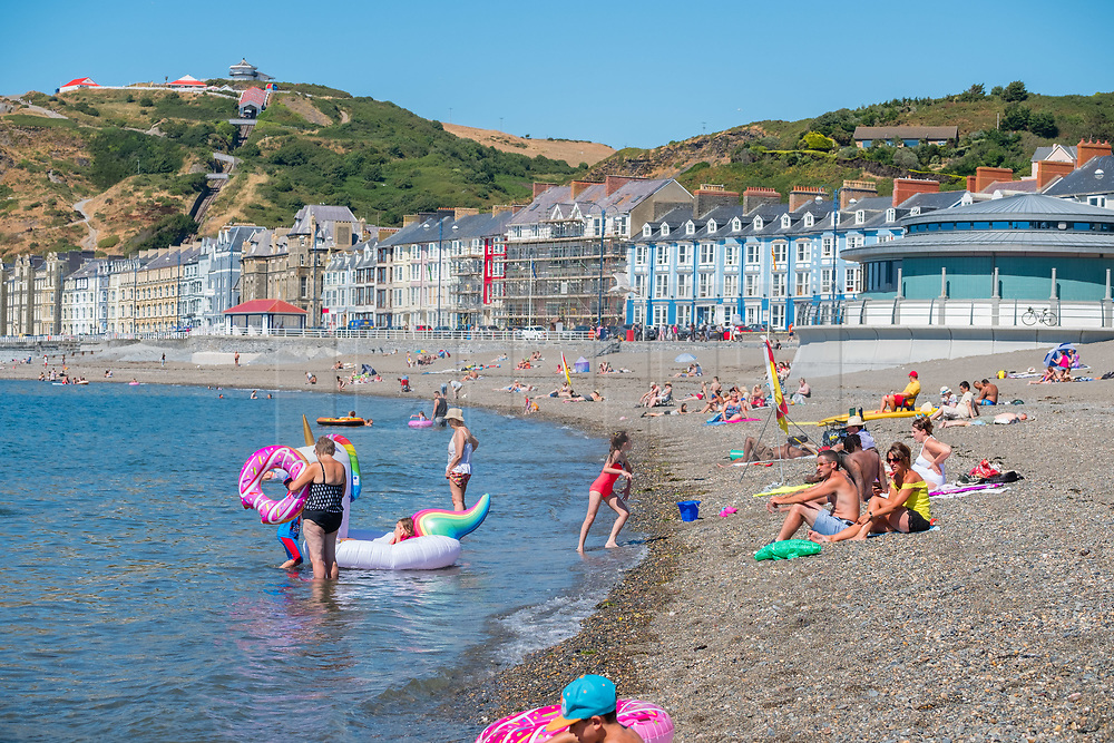 ©Licenced to London News Pictures<br /> Aberystwyth, UK. After a misty start, the afternoon in Aberystwyth is cloudless and sunny. People head for the seaside to relax in the sunshine and to cool off in the crystal clear waters of Cardigan Bay. Over much of the UK  the prolonged  heat wave and very dry weather continues unbroken, with temperatures expected to climb again towards 30ºc or higher by the end of the week. Photo credit Keith Morris / LNP