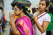 22 DECEMBER 2012 - SINGAPORE, SINGAPORE:  Women pray at Sri Veeramakaliamman Temple, a Hindu temple located in Little India in Singapore. The Sri Veeramakaliamman Temple is dedicated to the Hindu goddess Kali, fierce embodiment of Shakti and the god Shiva's wife, Parvati. Kali has always been popular in Bengal, the birthplace of the labourers who built this temple in 1881. Images of Kali within the temple show her wearing a garland of skulls and ripping out the insides of her victims, and Kali sharing more peaceful family moments with her sons Ganesha and Murugan. The building is constructed in the style of South Indian Tamil temples common in Tamil Nadu as opposed to the style of Northeastern Indian Kali temples in Bengal.      PHOTO BY JACK KURTZ