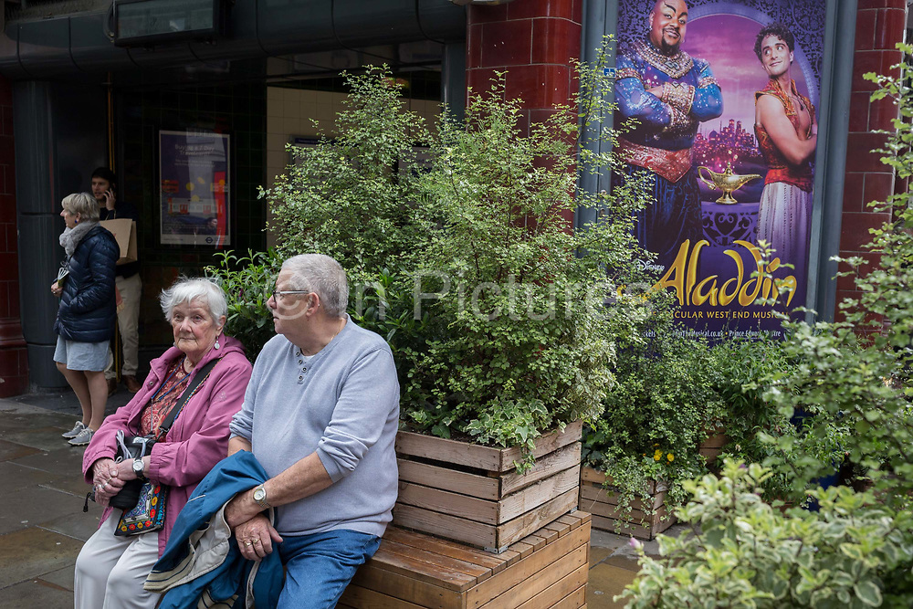 An elderly couple rest on a bench in front of Covent Garden Underground station, and next to a poster advertising the musical, Aladdin, on 15th June 2019, in London, England.