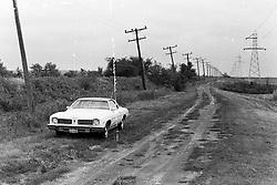 "1975 - 1977 Heyworth Illinois<br /> 1974 Pontiac sitting near ""Shankel's Pond on old interurban railroad track property.<br /> <br /> Archive slide, negative and print scans."