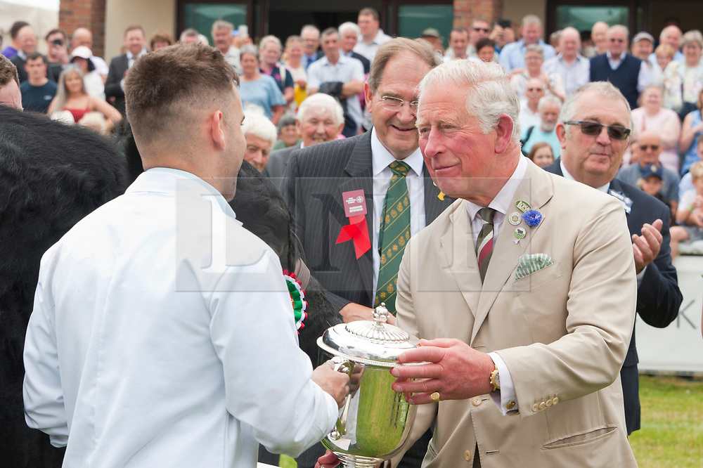 © Licensed to London News Pictures. 22/07/2019. Llanelwedd, Powys, UK. Prince Charles presents prizes in the cattle ring. HRH Prince Charles, Prince of Wales, and Her Royal Highness, Camilla Parker Bowles, The Duchess of Cornwall visit the Royal Welsh Agricultural Show on the first day of the 100th Royal Welsh Agricultural Show. The Royal Welsh Agricultural Show is hailed as the largest & most prestigious event of its kind in Europe. In excess of 200,000 visitors are usually expected for the annual four day show period. The Royal Welsh Agricultural Society was founded in 1904. Photo credit: Graham M. Lawrence/LNP