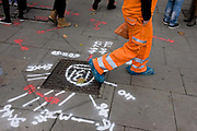 High-visibility workman walks over pavement markings. Crossing the paving stones on which another workman has sprayed coded symbols and numbers st the site of a manhole drains cover, the man wears a hi-visibility suit and plastic coverings on each boot. Other Londoners walk around this crossing at Holborn in central London.