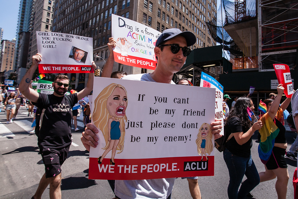 "New York, NY - 25 June 2017. New York City Heritage of Pride March filled Fifth Avenue for hours with groups from the LGBT community and it's supporters. Marchers from the ACLU with signs that read ""If you cant be my friend just please dont be my enemy!"", and bearing a caricature of Kelly Anne Conway; and ""Girl, look how orange you fucking look girl!"", bearing a photo of Donald Trump."