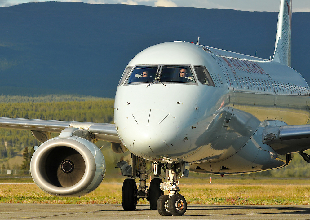 Air Canada Embraer 190 taxiing in the setting sun at Whitehorse International Airport, Yukon.