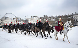 © Licensed to London News Pictures. 01/03/2018. London, UK. The Blues and Royals of the Household Cavalry Mounted Regiment cross a snowy Horse Guards Parade in central London. The 'Beast from the East' and Storm Emma have brought extreme cold and heavy snow to the UK. Photo credit: Peter Macdiarmid/LNP