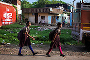 Ahead of morning lessons, Jyoti, 14, (left) and her younger sister Poonam, 13, (right) are walking towards the small, private school they regularly attend since 2011, located close to their newly built home in Oriya Basti, one of the water-contaminated colonies in Bhopal, Madhya Pradesh, India, near the abandoned Union Carbide (now DOW Chemical) industrial complex. The two girls are studying in Year 6, out of 12, in 2015-16.