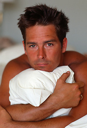 Handsome shirtless man holding a pillow