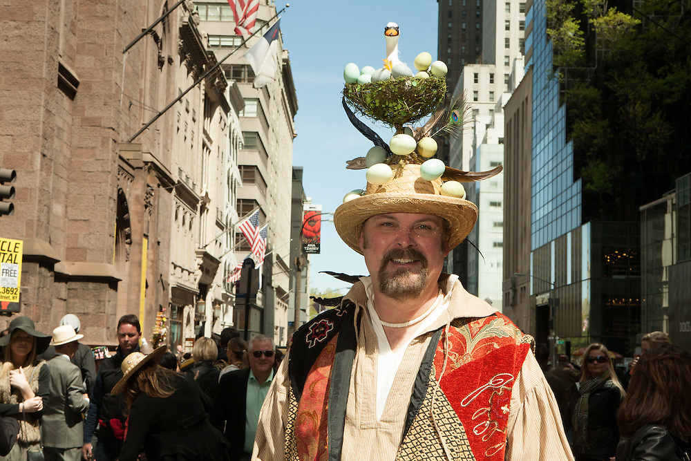 A man wearing a tall hat including a nesting goose and many eggs.