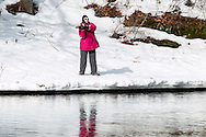 Cuddebackville, New York - A woman fishes in the Neversink River on the opening day of trout season in New York State. Most of the riverbank is still covered in snow and ice.