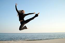 woman in midair dancing by the ocean