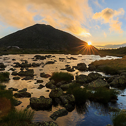The sun emerges from behind Mount Madison as seen from Star Lake in New Hampshire's White Mountain National Forest. Appalachian Trail.