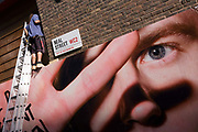 A giant eye from a construction site hoarding watches street next to a workman up a ladder on Neal Street, London. The workman stands on top of the hoarding structure and attends to a detail in the shop's frontage, equipped with tools that hang from his belt. Below him is the large-scale face being covered by the model's hand and whose fingers are open wide across his right eye. His left is seen gazing across the city - almost an Orwellian scenario of the writer's 'Big Brother' story from 1984.