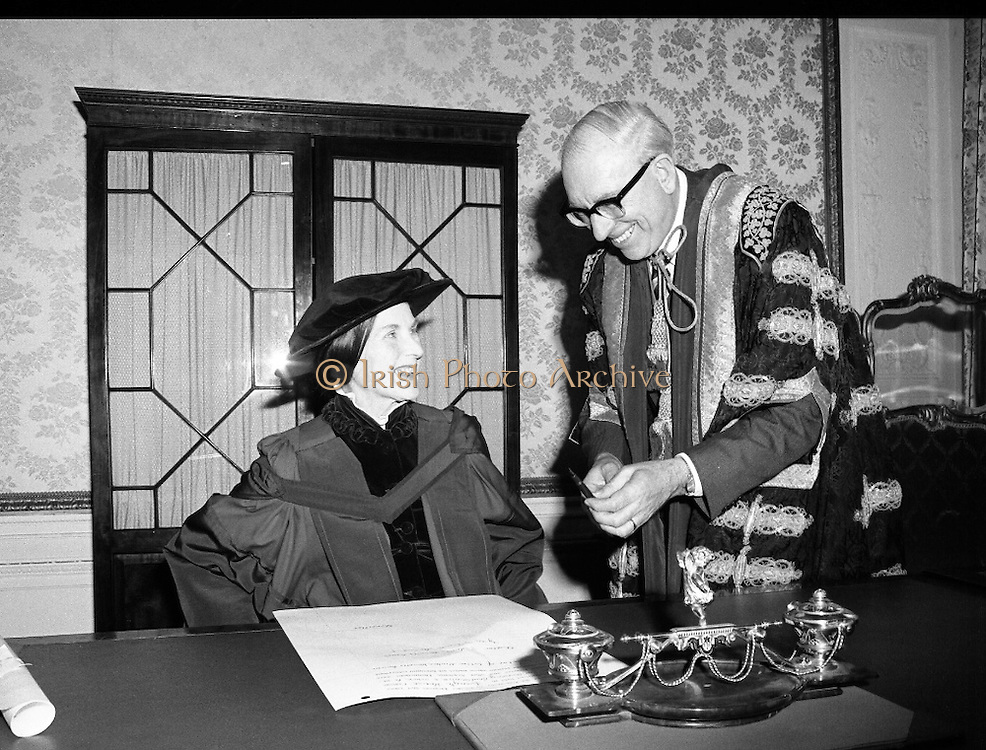 Honorary Degree For Joan Denise Moriarty.    (M65)..1979..05.04.1979..04.05.1979..5th April 1979..Joan Denise Moriarty, was an Irish ballet dancer, choreographer, teacher of ballet, and traditional Irish dancer and musician. She was the founder of professional ballet in Ireland. Her achievements were rewarded by the conferring of an honorary degree at University College ,Cork...Image shows Ms Moriarty signing the scroll accepting the conferring of the Honorary Degree from U.C.C.,also in the image is Dr T.K.Whittaker,Chancellor of the National University of Ireland.