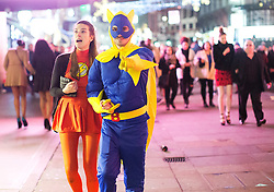 © Licensed to London News Pictures. 01/01/2015. A couple of revellers dressed up as superheroes enjoy a night out in central London to celebrate New Years Day. Photo credit : Isabel Infantes / LNP