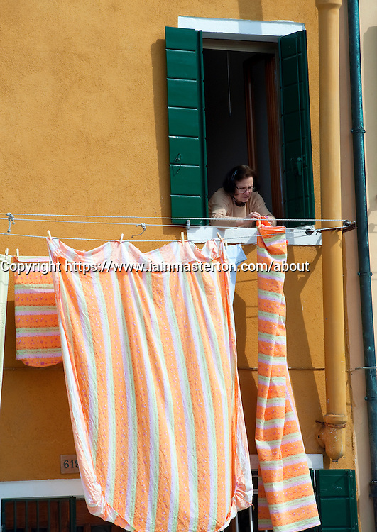 Woman hanging out sheets to dry on washing line in house in Burano Italy