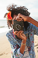 An African American woman pointing a plastic toy camera.