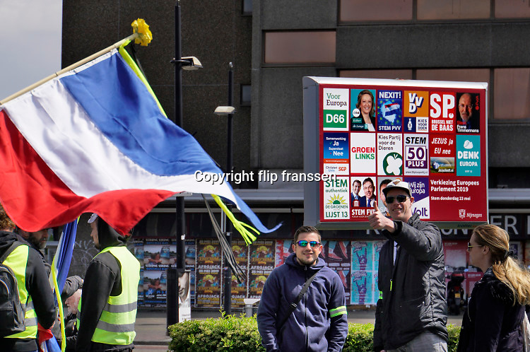 Nederland, Nijmegen, 11-5-2019 Landelijke demonstratie van Gele Hesjes door de binnenstad. Hoewel de opkomst wat tegenviel vetrok de bonte stoet vanaf het station naar Plein44 . Op de achtergrond een verkiezingsbord met verkiezingsaffiches voor de europese verkiezingen . Foto: Flip Franssen.