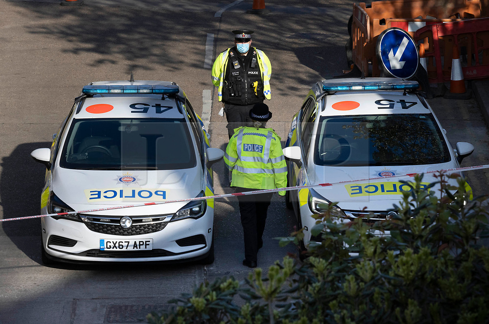© Licensed to London News Pictures. 23/04/2021. Walton-on-Thames, UK.  Police continue to guard the scene at the car park of a Marks and Spencer store in Walton-on-Thames after a man was killed in an altercation. Police were called to Church Street around 2.15pm on 22/04/2021 following reports that an altercation had taken place between a group of men. One of the men then got into his car, a white 1 series BMW, and is reported to have driven at two of the other men in the group.  One man was killed and another injured. The driver of the car has been arrested on suspicion of murder and attempted murder. Photo credit: Peter Macdiarmid/LNP