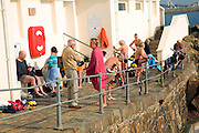 Sea swimmers drying and dressing after their bathe, St Peter Port, Guernsey, Channel Islands, UK