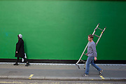 Street Scene of people passing by a green painted wall on in Soho, London, England, United Kingdom. The simplicity of the scene helps highlight the figures of ordinary people going about their daily lives. Man carrying a ladder.
