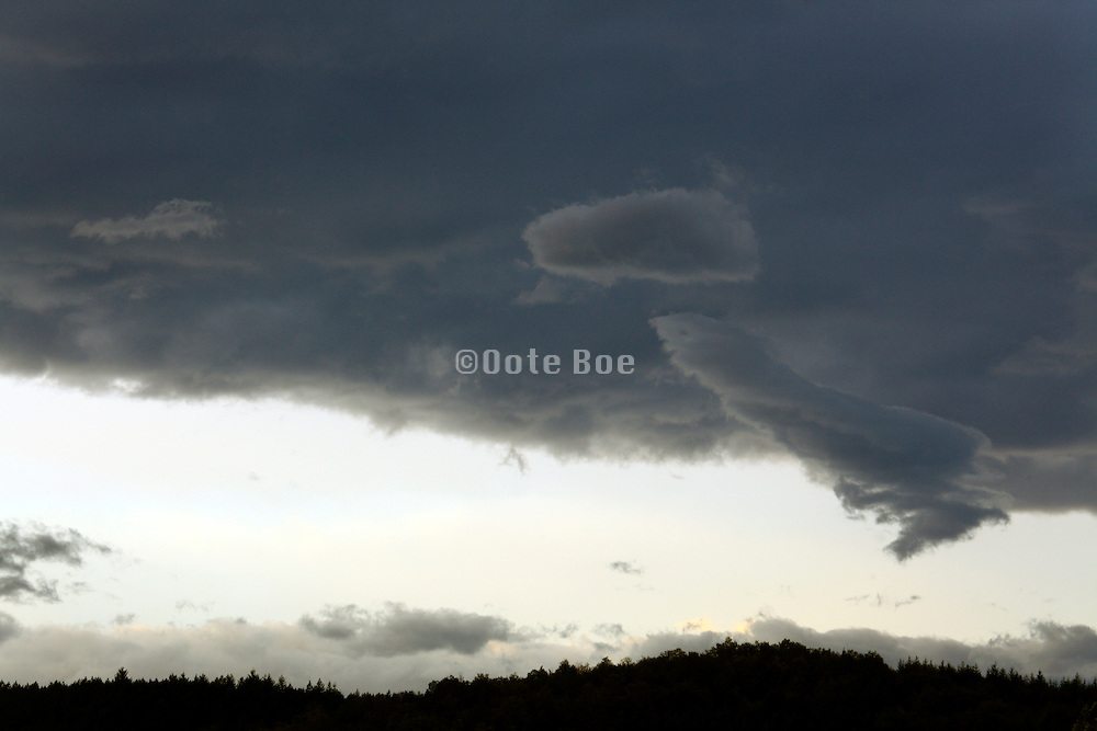 dark clouds hanging above a silhouette hilly landscape