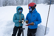 Diamond Peaks Ski Patrol members Teal Wyckoff and Owen Richard evaluate snowpack conditions near Montgomery Pass by observing layers in a snowpit, Feb. 6, 2021.