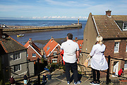 199 steps up to the East Cliff. Once these stairs used to be wooden and were constructed to help pallbearers carrying coffins on the climb up to St Mary's Churchyard. Whitby is a seaside town, port in the county of North Yorkshire, originally the North Riding. Situated on the east coast at the mouth of the River Esk. Tourism started in Whitby during the Georgian period and developed. Its attraction as a tourist destination is enhanced by its proximity to the high ground of the North York Moors, its famous abbey, and by its association with the horror novel Dracula. Yorkshire, England, UK.