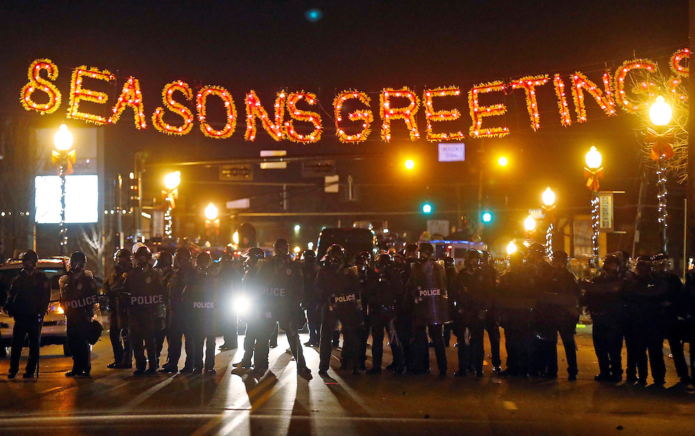 Police officers block a street during rioting after a grand jury returned no indictment in the shooting of Michael Brown in Ferguson, Missouri, early November 25, 2014. Gunshots were heard and bottles were thrown as anger rippled through a crowd outside the Ferguson Police Department in suburban St. Louis after authorities on Monday announced that a grand jury voted not to indict a white officer in the August shooting death of an unarmed black teen.   REUTERS/Jim Young