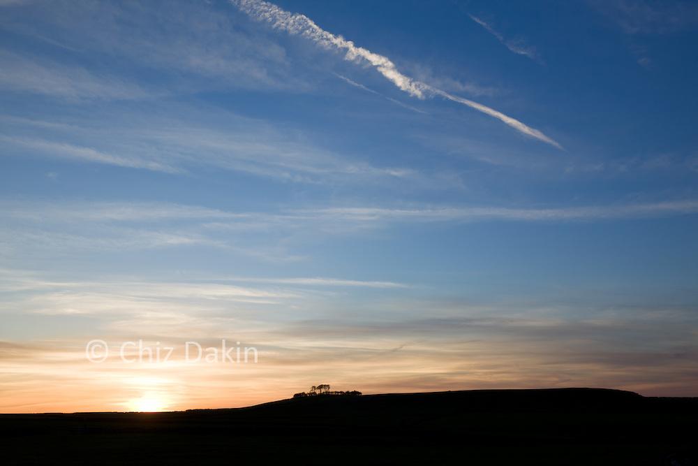 Sunset hilltop silhouette over Minninglow, Derbyshire Peak District.