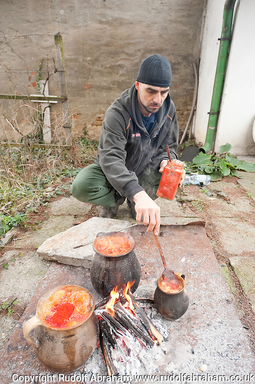 Local tanner György Farkas cooking bableves (traditional bean stew) in clay pots in his garden. Busó carnival, Mohács, Hungary © Rudolf Abraham