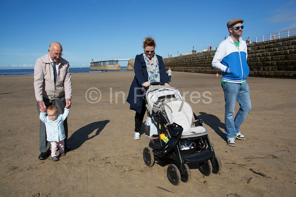 Three generations of one family walking on the beach at Whitby. From right to left: Daniel Bowater (37), husband to Kate Bowater (34), alongside her grandad, Joseph Thomas (90) and their daughter, Ella Catherine Bowater (10 months). Whitby is a seaside town, port in the county of North Yorkshire, originally the North Riding. Situated on the east coast at the mouth of the River Esk. Tourism started in Whitby during the Georgian period and developed. Its attraction as a tourist destination is enhanced by its proximity to the high ground of the North York Moors, its famous abbey, and by its association with the horror novel Dracula. Yorkshire, England, UK.