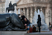 With the columns of St. Martin-in-the-Fields church and the statue of a military hero in the background, a young women pushes her friend up on to a lion in Trafalgar Square, on 9th December 2019, in London, England.