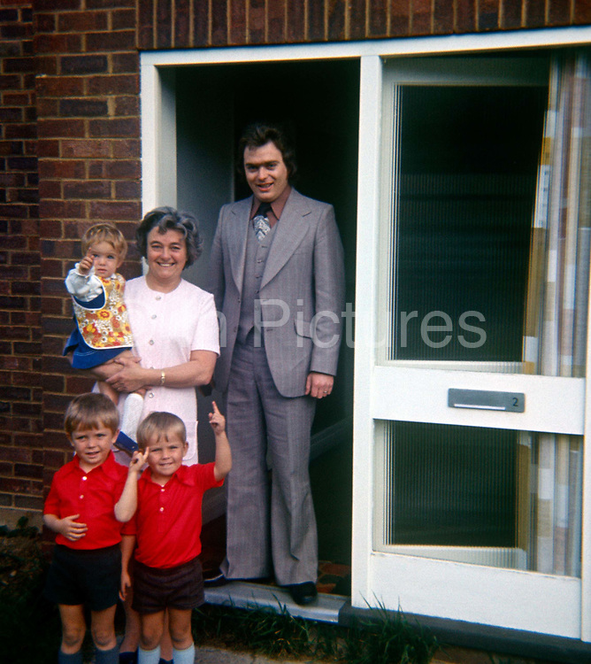 A portrait of family standing in the doorway of a detached home in the 1970s. Two brothers dressed in identical red shirts point upwards and their sister points in another direction while their grandmother stands next to the childrens' uncle in the doorway of this detached home in Kent. The man wears the height of 70s fashion - a 3-piece suit (with waistcoat) with flared trousers and a  brown shirt. The picture shows us a memory of nostalgia in an era from the last century.