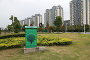 An utility box wrapped up with pictures of trees stands near a residential housing complex in Yangzhou, Jiangsu Province, China on 19 July 2012. While the Chinese government has tried various ways to cool down the property market, real estate prices have still seen a steady increase in recent years, proving hard for the country to move away from an investment driven economy.