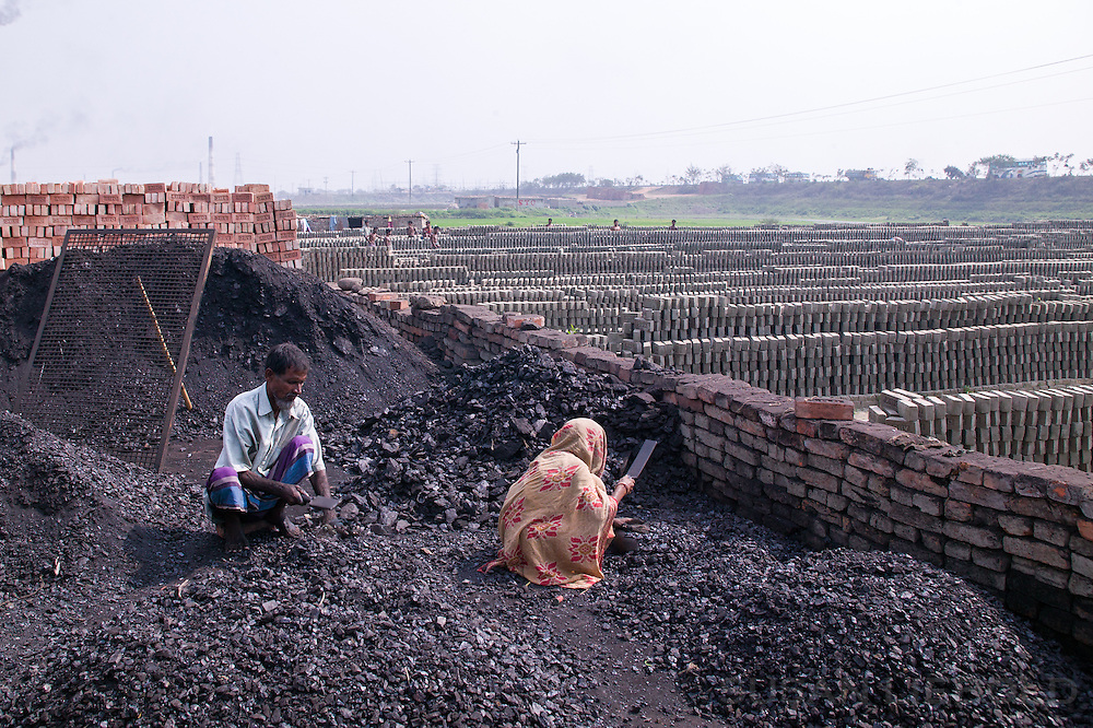 Two people breaking coal into small pieces to burn in the kiln, Bangladesh.