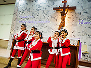 "23 DECEMBER 2018 - CHANTABURI, THAILAND: Girls playing dancing Santas in the Christmas pageant pose for pictures in a chapel at the Cathedral of the Immaculate Conception's Christmas Fair in Chantaburi. Cathedral of the Immaculate Conception is holding its annual Christmas festival, this year called ""Sweet Christmas @ Chantaburi 2018"". The Cathedral is the largest Catholic church in Thailand and was founded more than 300 years ago by Vietnamese Catholics who settled in Thailand, then Siam.  PHOTO BY JACK KURTZ"