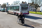 The  wife of a prisoner getting off a bus to vist her husband in HMP Portland. Dorset, United Kingdom.