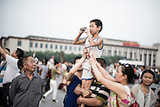 A Chinese family raises up his son to let him take a picture in Tiananmen Square in Beijing, China, July 19, 2014.<br /> <br /> Smartphones are an essential tool of Chinese ordinary life. Everywhere in China, people use them to take pictures to share online, to talk and chat, to play videogames, to get access to the mainstream information, to get connected one each other. In the country where the main global social media are forbidden - Facebook, Twitter and Youtube are not available  -, local social networks such as WeChat have a wide spread all over the citizens. The effect is an ordinary and apparently compulsive way to get easy access to digital technology and modern way of communication. <br /> A life through the display. Yes, We Chat.<br /> <br /> © Giorgio Perottino